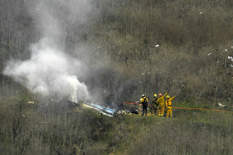 Firefighters work the scene of a helicopter crash where former NBA star Kobe ...