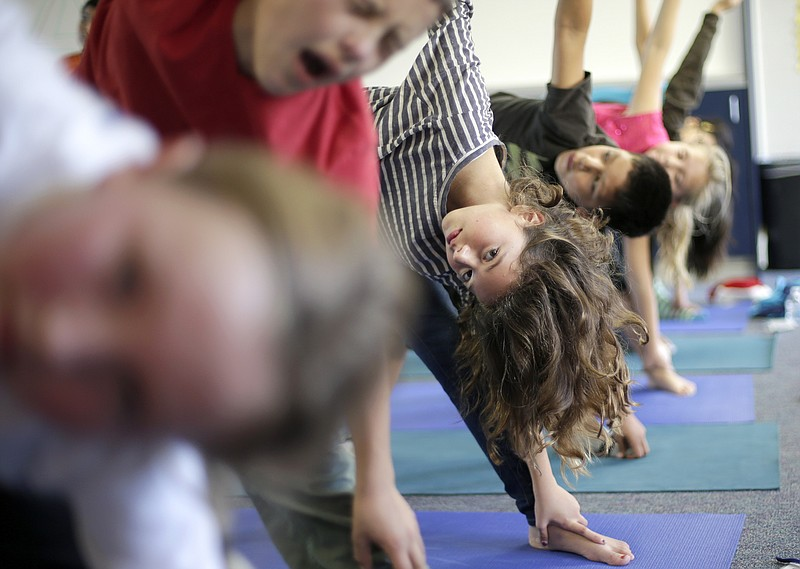 In this Dec. 11, 2012 file photo, students hold their position during a yoga ...