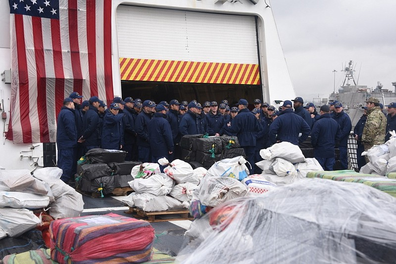 Coast Guardsmen gather together before preparing bails of cocaine to be offlo...