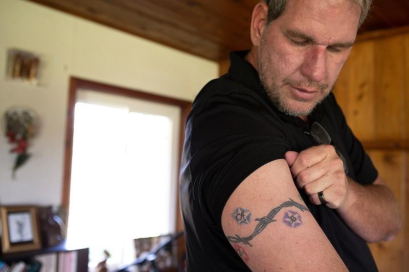 Andrew Simmons showing the tattooed the initials of all six of his adopted ch...