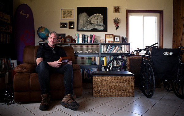 Andrew Simmons sits for a portrait in the family room of ...
