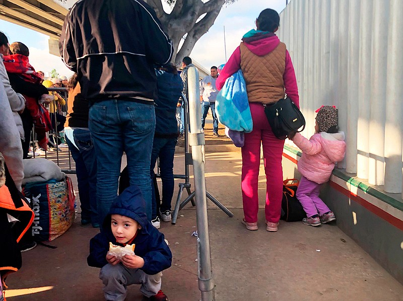 People seeking asylum in the United States wait at the border crossing bridge...