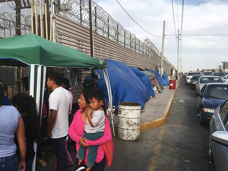 In this May 5, 2019, file photo, migrants walk between tents, left, and cars ...