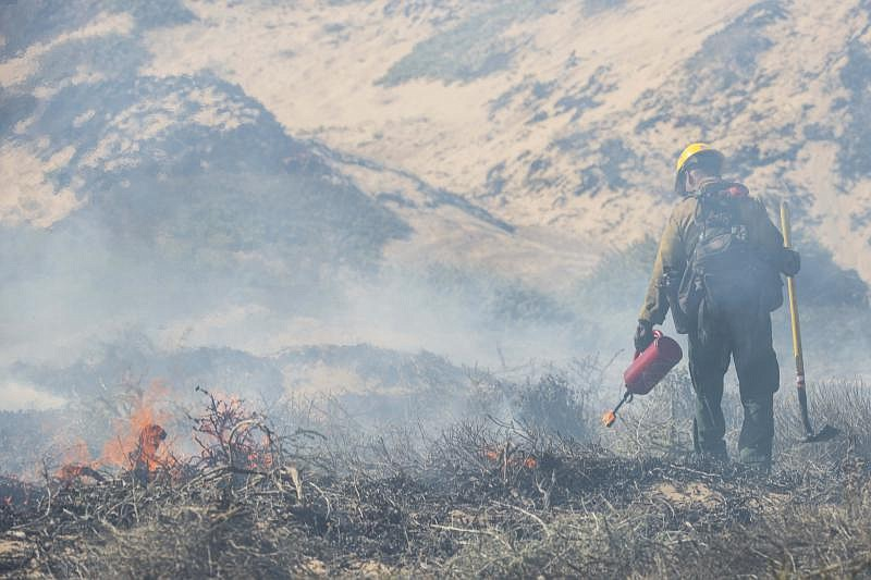 A fire fighter monitors a controlled burn Sept. 18, 2019 at Vandenberg Air Fo...