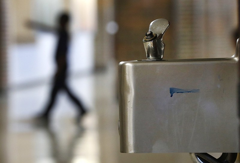 A student walks in the hallway past a water fountain at Noble School in Detro...