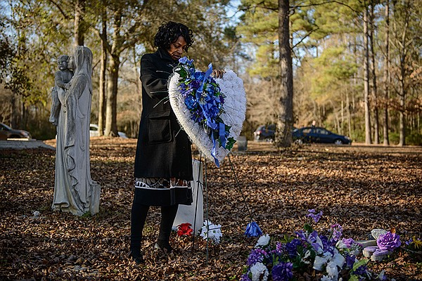 Claudia Lacy visits her son Lennon's grave.