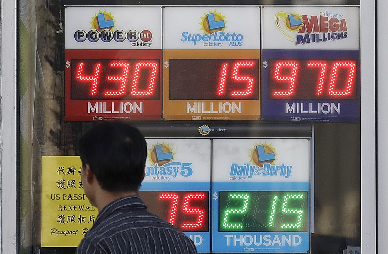 n this Oct. 18, 2018, file photo, a man walks past a lottery display outside ...