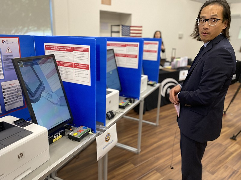 San Diego County Registrar of Voters Michael Vu stands next to a row of ballo...