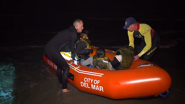Rescuers help passengers from a lifeguard boat in Del Mar...
