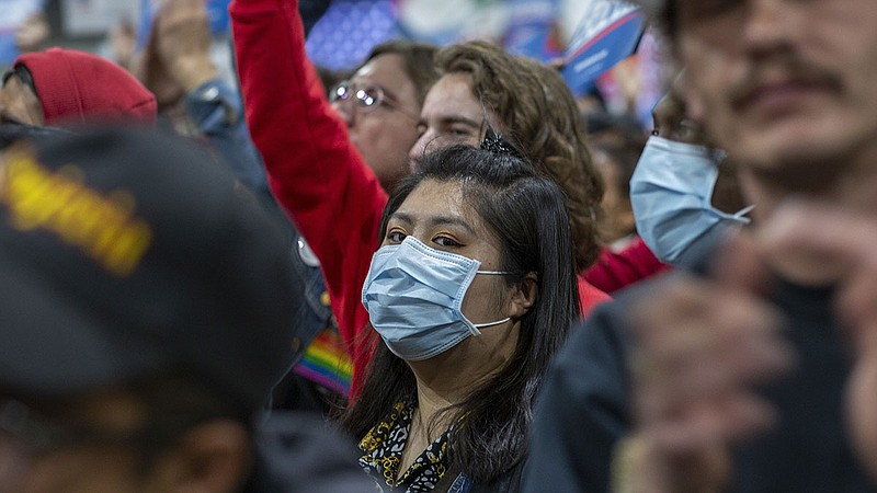 A woman in California wears a medical mask during a political campaign rally,...