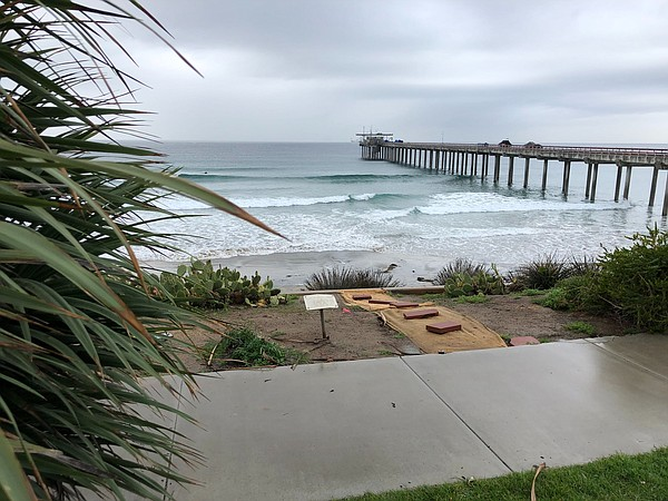 Rain lingers on the horizon behind Scripps Pier, which is...