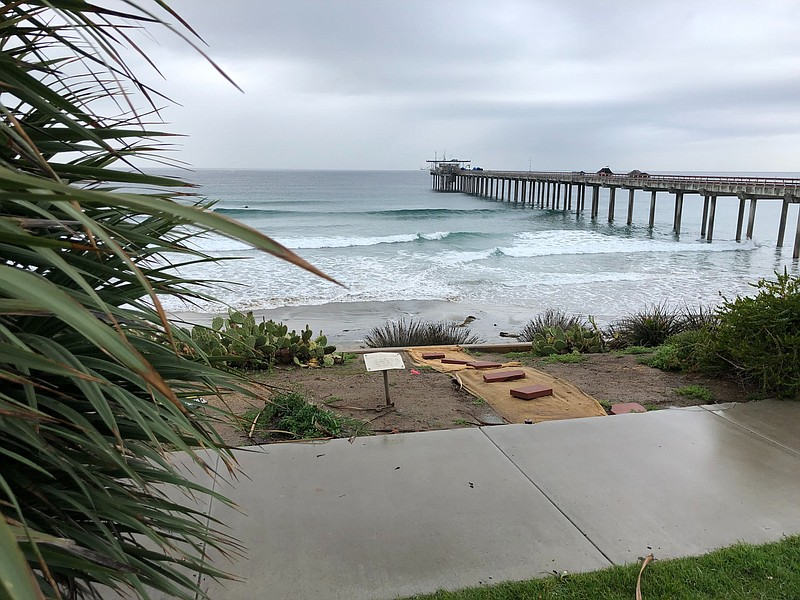 Rain lingers on the horizon behind Scripps Pier, which is where weather ballo...
