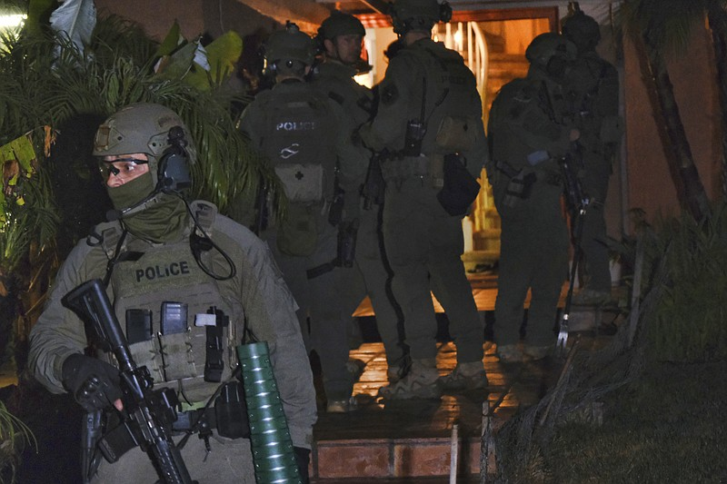 DEA agents search a residential house during an arrest of a suspected drug tr...
