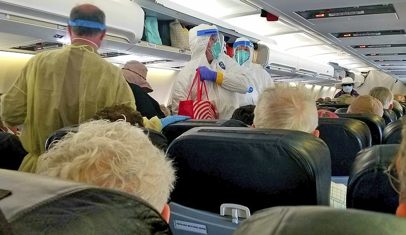 This photo by Michele Smith shows crewmembers in protective garb helping Gran...