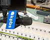 A microphone with a KPBS logo hangs over an aud...