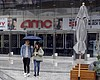 People exit an AMC theater Saturday, March 14, ...