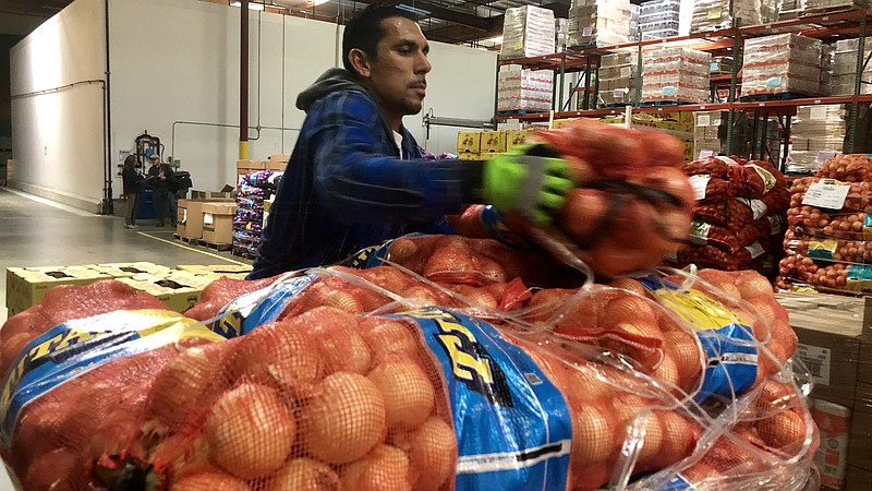 A Feeding San Diego employee loads onions onto a pallet, March 17, 2020.