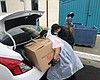 Two students load up a car outside the Zura Res...