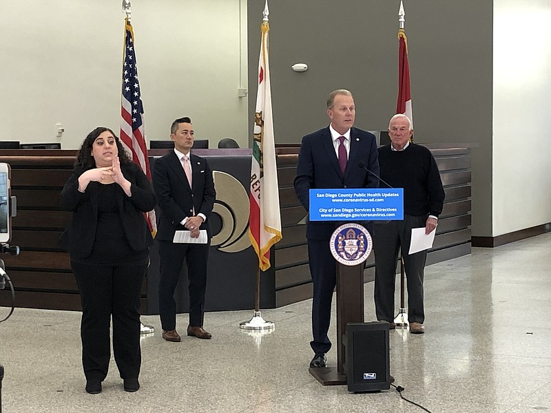 San Diego Mayor Kevin Faulcon (center) announcing a relief fund at City Hall ...