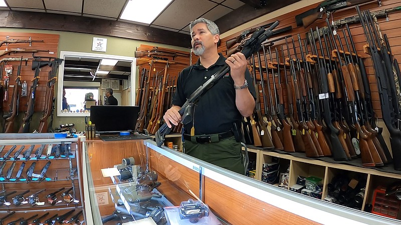 AO Sword Firearms owner David Chong displays a shotgun inside his El Cajon st...