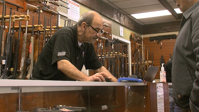 A customer looks at guns inside AO Sword Firearms in El Cajon, March 23, 2020.