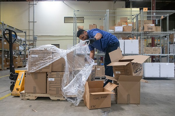 Warehouse supervisor Andres Castro unloads a delivery of ...