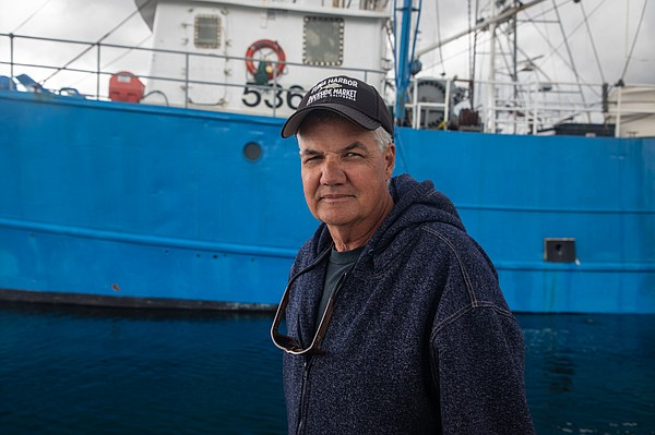 Commercial fisherman David Haworth stands on a dock in Sa...