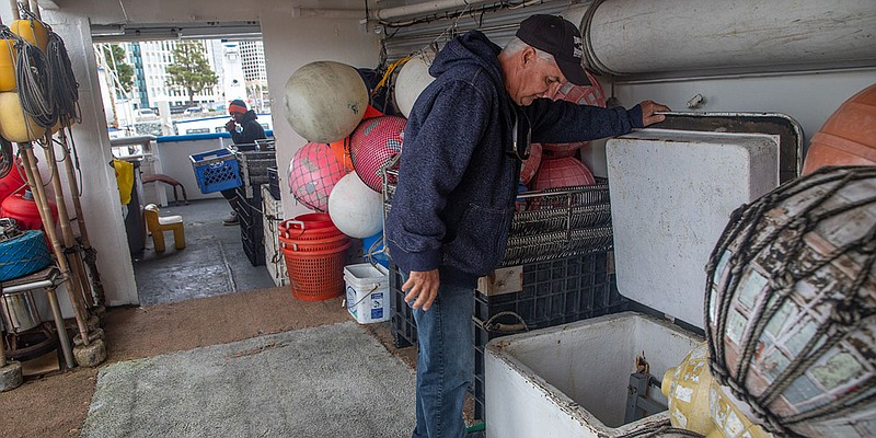 David Haworth looks into the supply hold of one of his fishing boats in San D...
