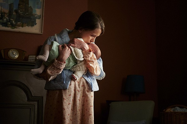 Marion (ELLIS WALLWORK) holding a baby