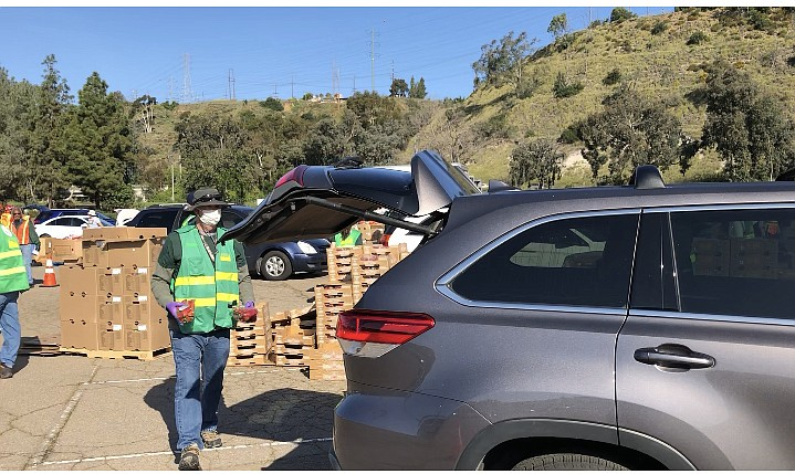 A volunteer fills the trunk of a minivan with food outside of SDCCU Stadium o...