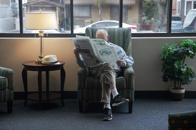 Walter Egger reads a newspaper in the common area at St. Paul's Manor in San ...