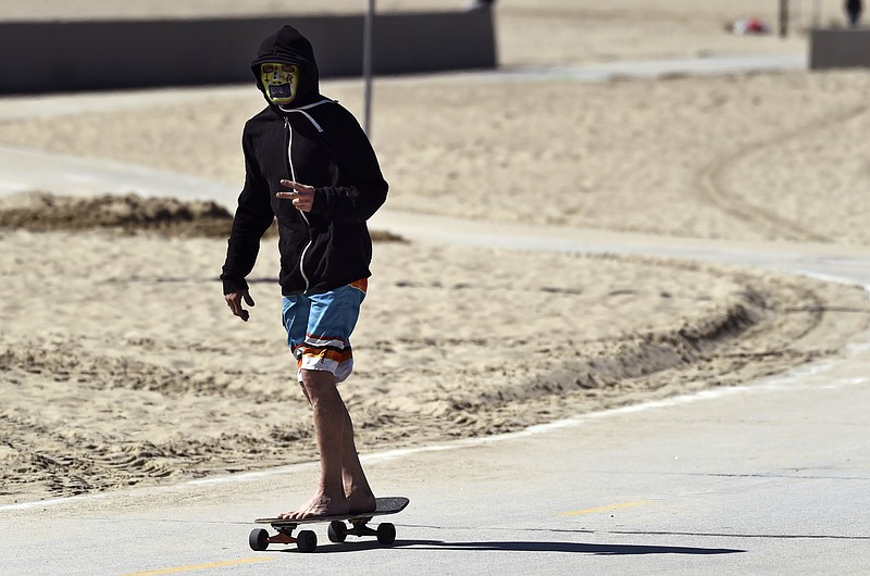 A skateboarder wears a face mask as he moves past Venice Beach, Monday, March...