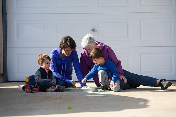 Lindsay Hartmann, left, plays with her two sons outside t...