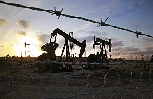 In this Thursday March 6, 2014, file photo, the sun sets beyond pumpjacks ope...
