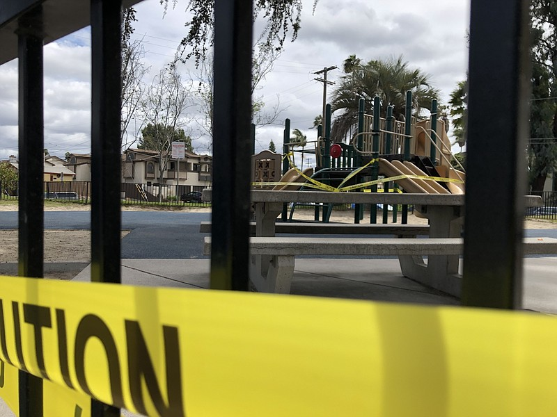 Caution tape surrounds a city park that was closed because of the coronavirus...
