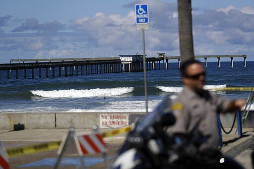 A police officer stands in front of a closed beach Tuesday, March 24, 2020, i...