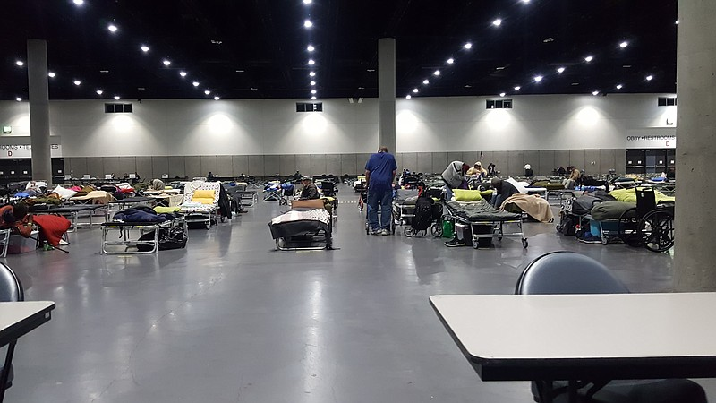 Cots line the San Diego Convention Center floor as it is converted into a hom...