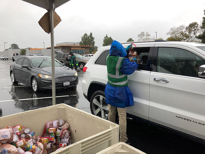 San Diego Food Bank workers distribute 25-lb packages of food to people in th...