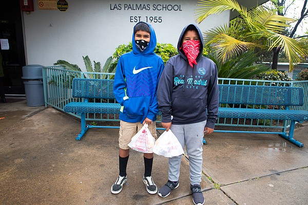 From left, Damian and Aahron Galicea pick up meals at Las...