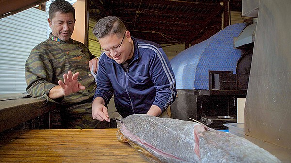 Host Jorge Meraz (right) carves up a fish with chef Migue...
