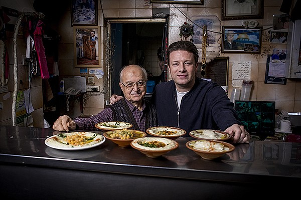 Host Jamie Oliver (right) learns about food cultures arou...