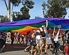 San Diego Pride attendees march during the para...
