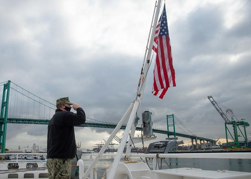 Sailor John Arkulary from Marshfield, Wis. salutes the flag aboard the hospit...