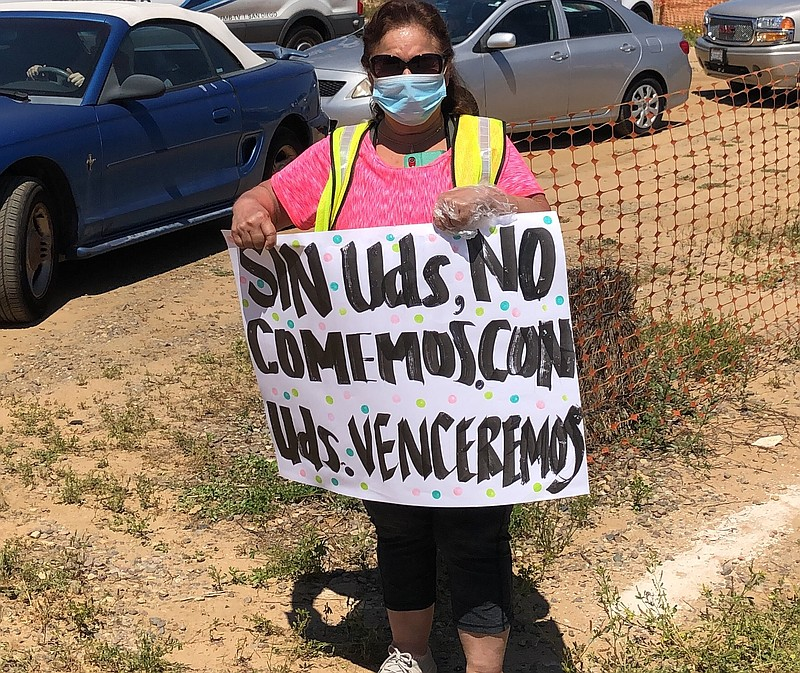 """A supporter of farm-workers in San Diego holds up a sign that translates to """"..."""