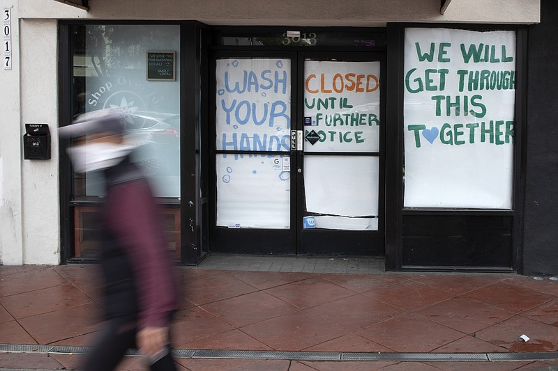 A man passes a store that closed as part of efforts to combat the spread of t...