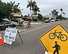 Two cyclists ride on Diamond Street past signs ...