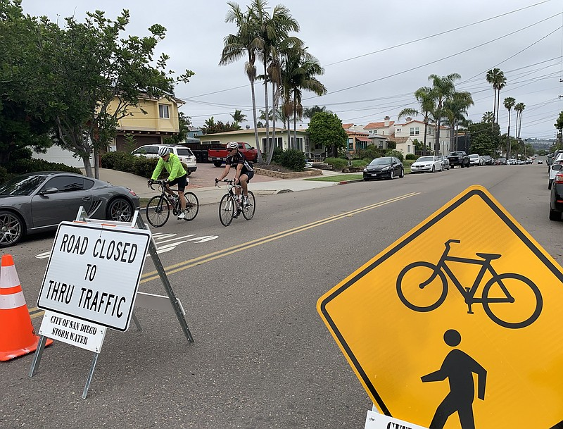 Two cyclists ride on Diamond Street past signs indicating it is closed to thr...