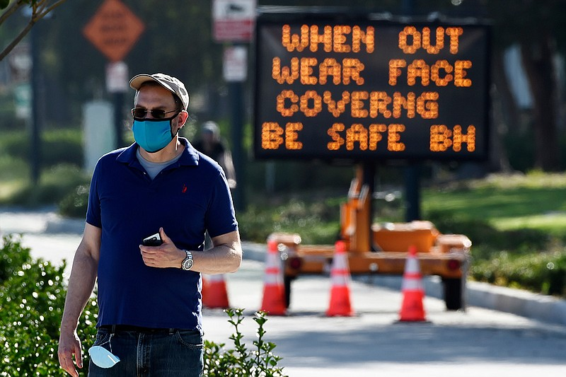 An electronic sign on Santa Monica Boulevard reminds people to wear masks to ...