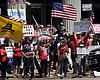 People hold signs and flags during a protest ag...