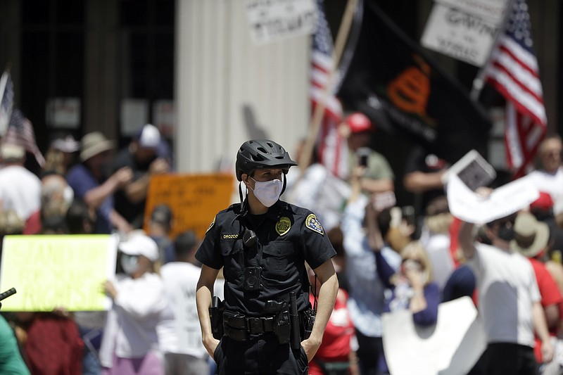 A San Diego police officer looks on during a protest against measures aimed a...